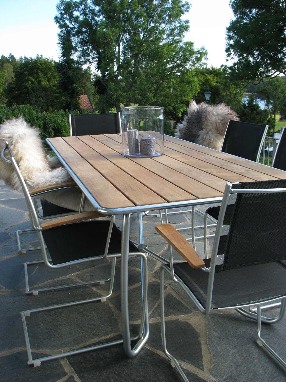 Spring matgrupp med rektangulärt matbord i teak och stolar med svart textilene.