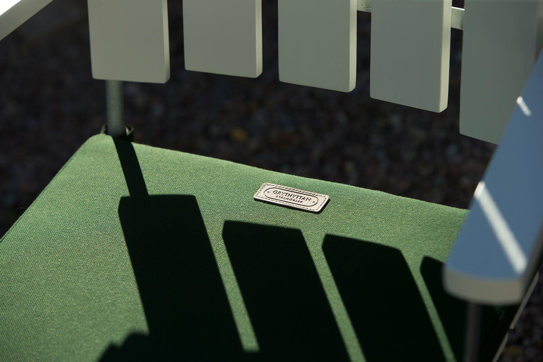A2 fåtölj i vitlackad ek med grön sittdyna.