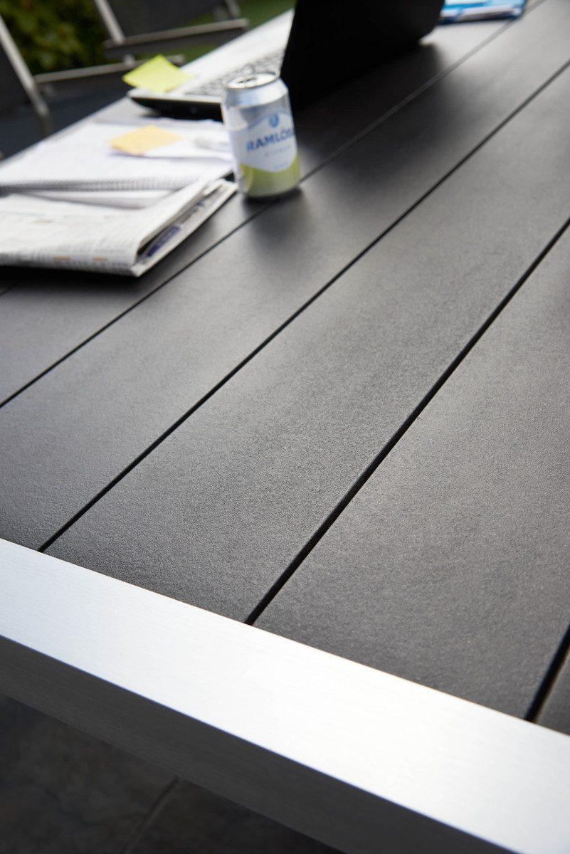 Detaljbild på Crescendo matbord med borstat aluminiumstativ och svart skiva.