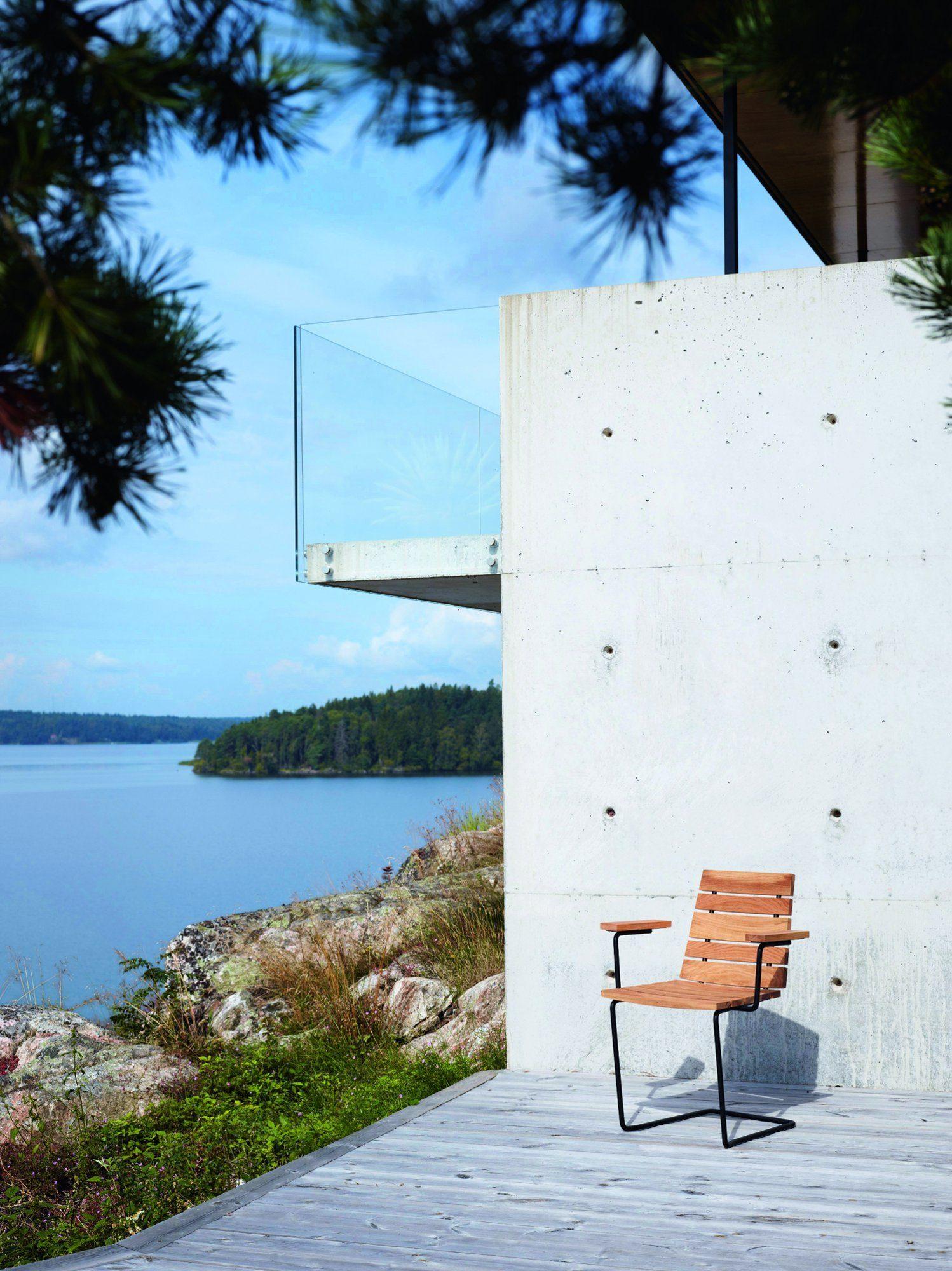 Grinda karmstol i teak med svart fjäderstål mot en betongvägg.