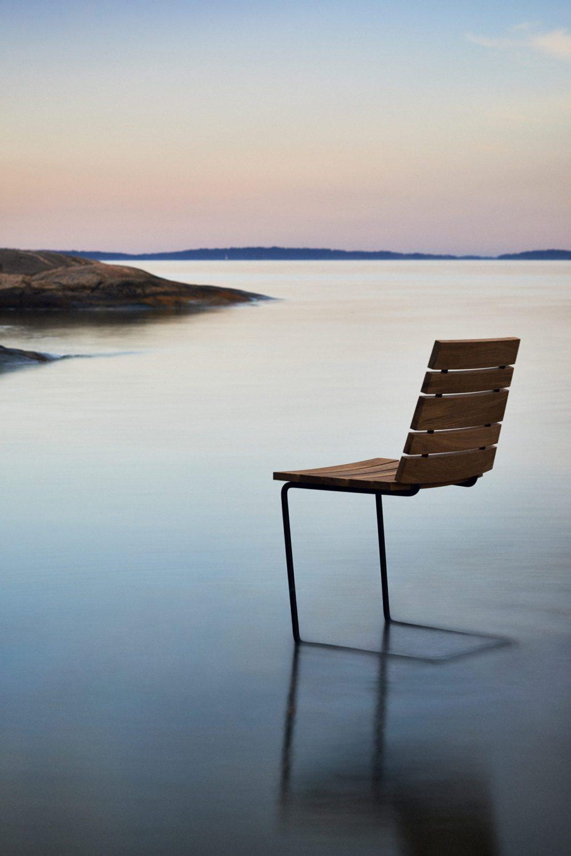 Grinda stol i teak och svart fjäderstol på en is.