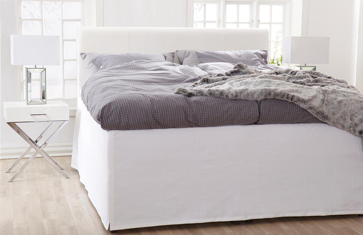 Ekhamra sänggavel i vitt lambada läder med vita sömmar.
