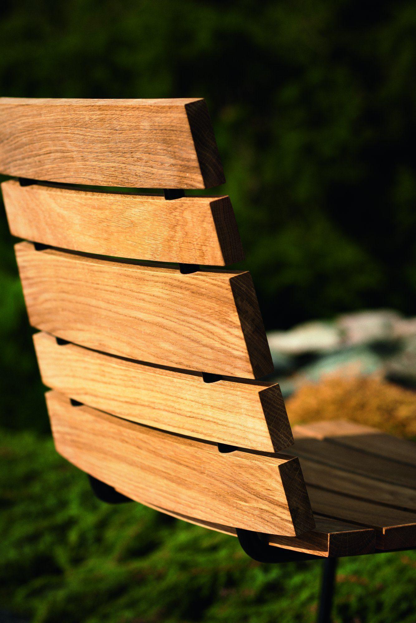 Detaljbild på Grinda stolen i teak med svart fjäderstål.