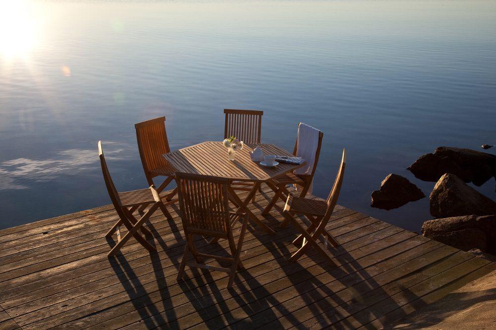 Viken teakgrupp med sex stolar och ett bord på en brygga.