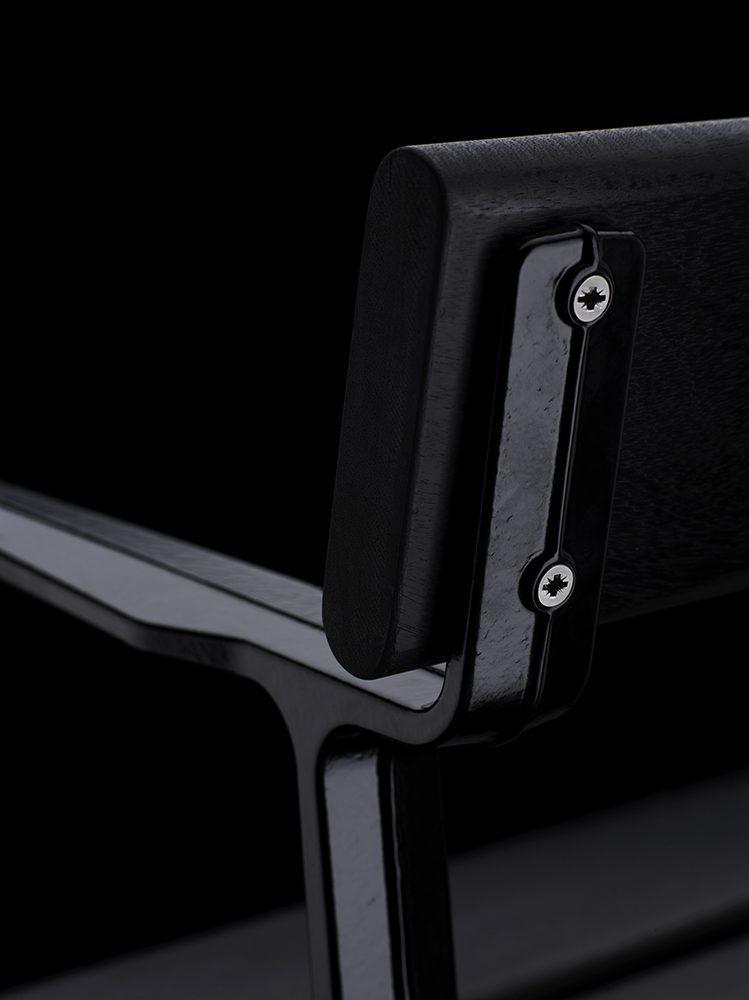 Detaljbild på Piccolo soffa i svartlaserad mahogny med svartlackad stativ.