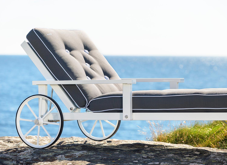 Närbild på en vit liggvagn från Fri Form med grå dyna.