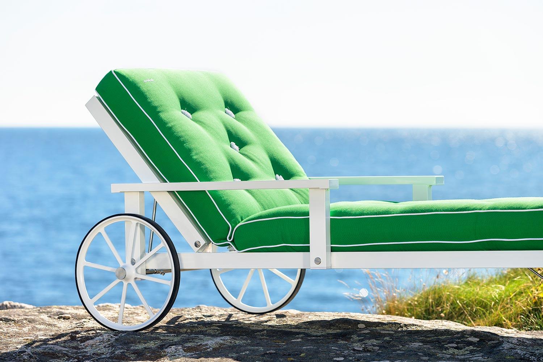Närbild på en vit liggvagn från Fri Form med grön dyna.