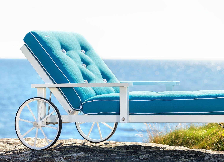 Närbild på en vit liggvagn från Fri Form med blå dyna.