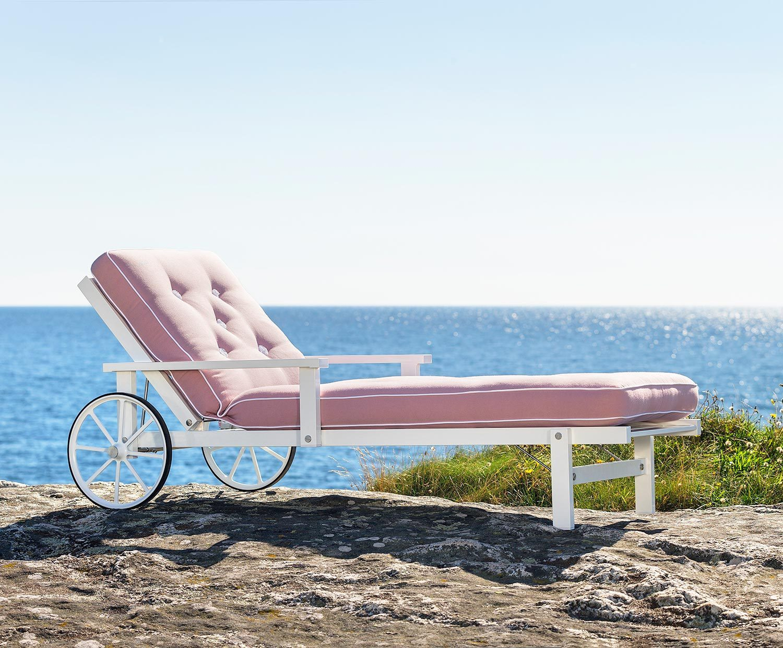 En vit liggvagn från Fri Form med rosa dyna.
