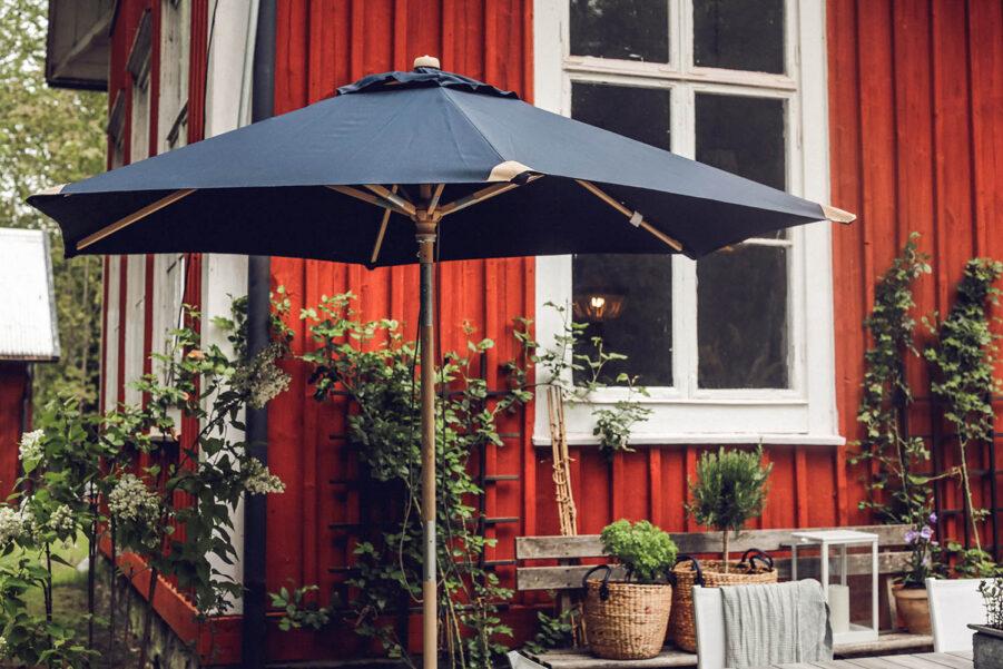 Miljöbild på Trieste parasoll i färgen Marin.