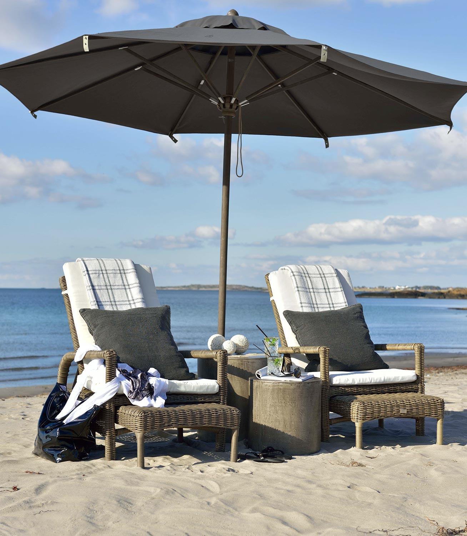 Tampa solstolar från Artwood i konstrotting tillsammans med Doloma sidobord och Portofino parasoll.