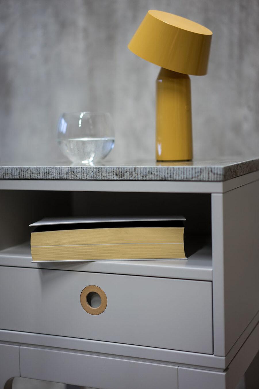 Miljöbild på Höllviken sängbord i ljusgrått med kalkstensskiva.