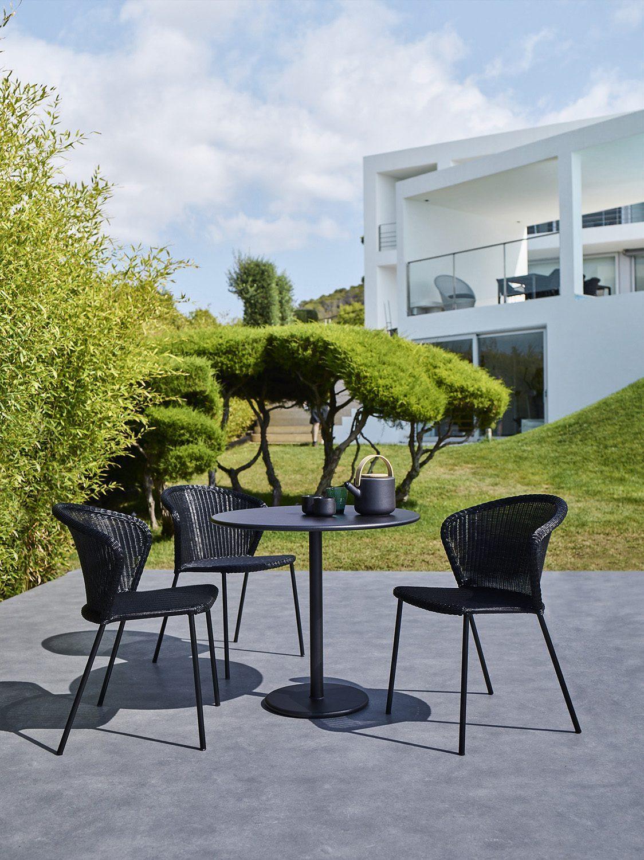 Lean stapelbar stol i konstrotting från Cane-Line tilsammans med Go cafébord.