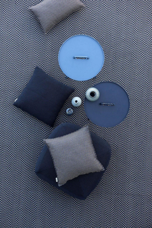 Blåa artiklar från Cane-Line. On-The-Move sidobord, Defined matta och Divine sittkudde.