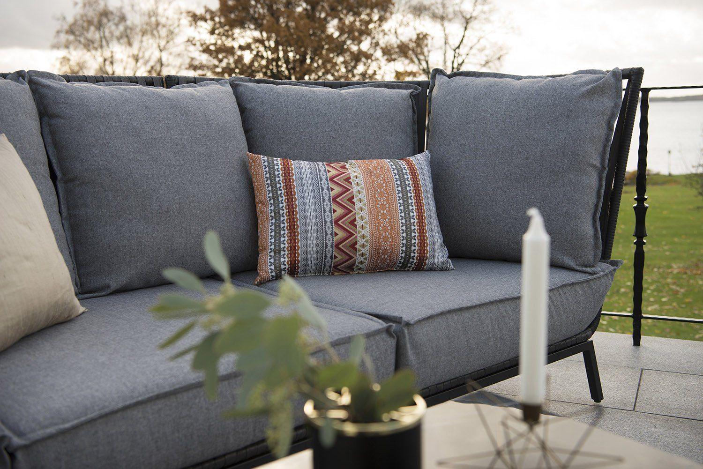 Jet Set soffa med gråmelerade dynor.