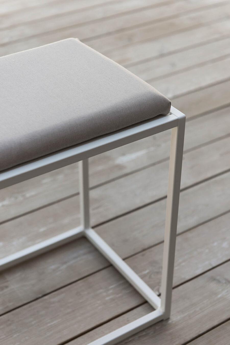 Design of bänk vit med beige dyna.