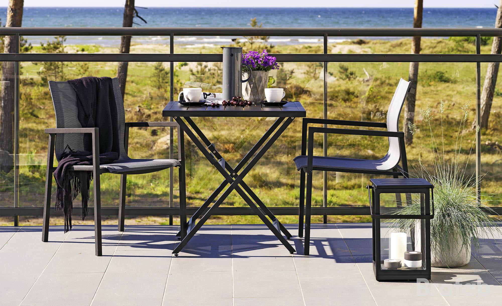 Miljöbild på Wilkie bord och Belfort stolar och ljuslykta i svart.