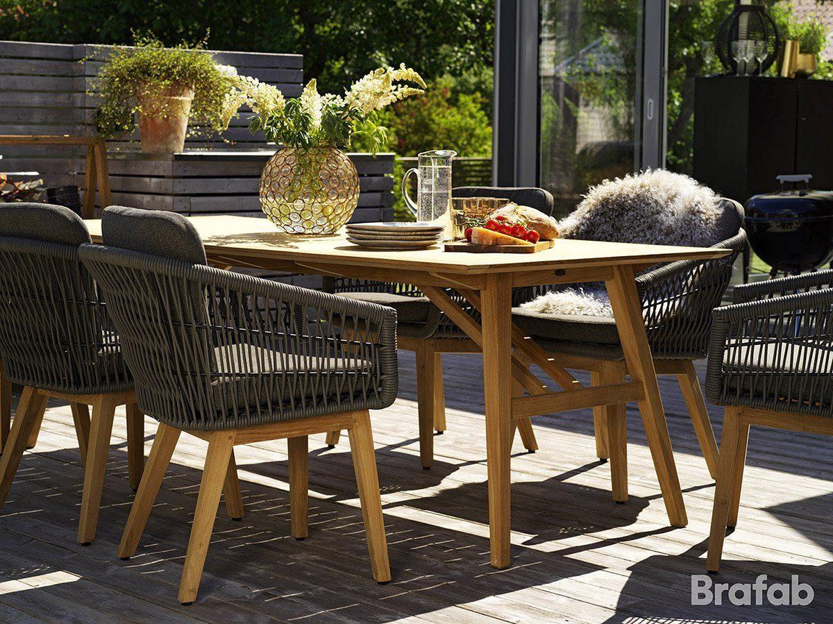 En miljöbild på Kenton karmstol i konstrotting och teak tillsammans med matbordet Chios från Brafab.