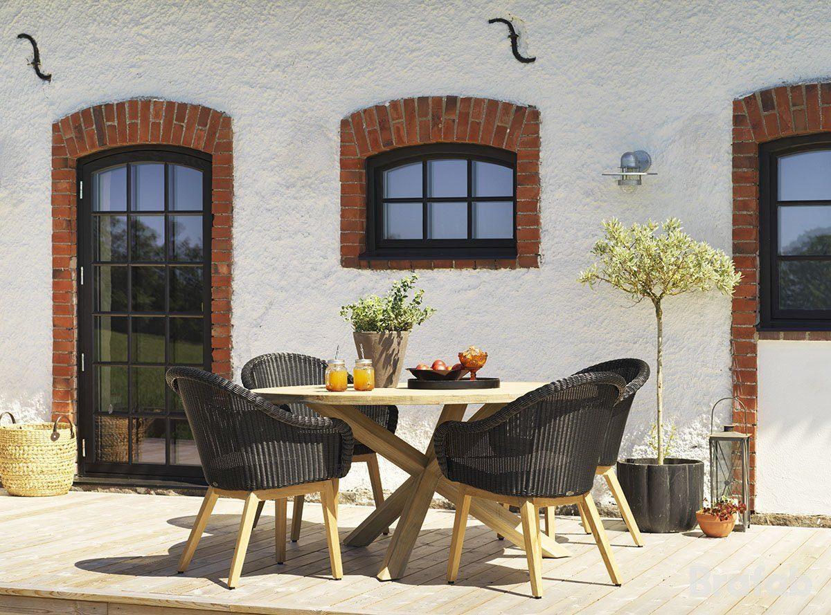 Miljöbild av stolarna Beverly i konstrotting och teak tillsammans med teakbord Eios.