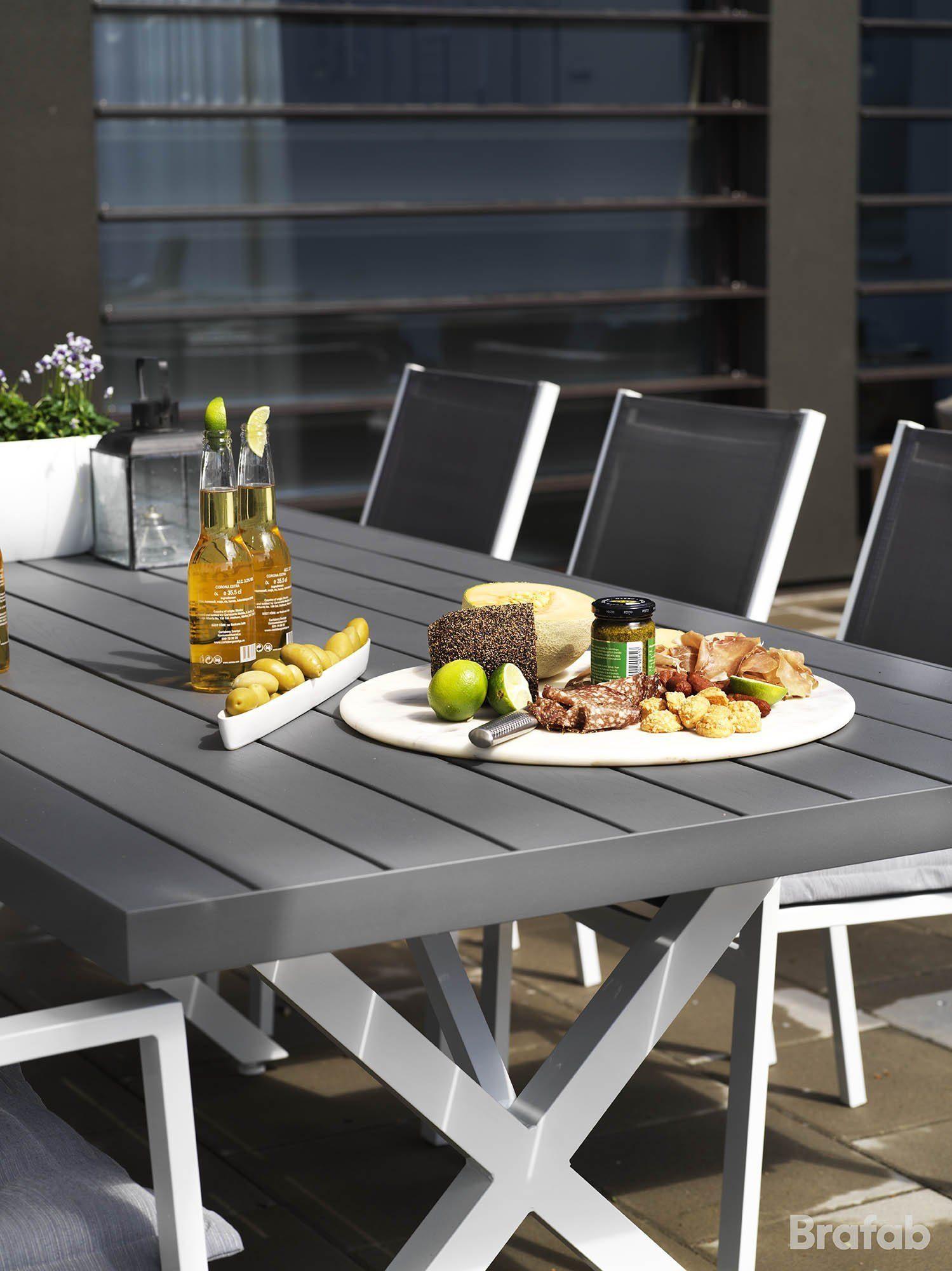 Miljöbild på matgrupp med möbler ur serierna Leone och Weldon, stolarna äör tillverkad i aluminium med sitsar i tectilene och bordet i vit och grå aluminium.