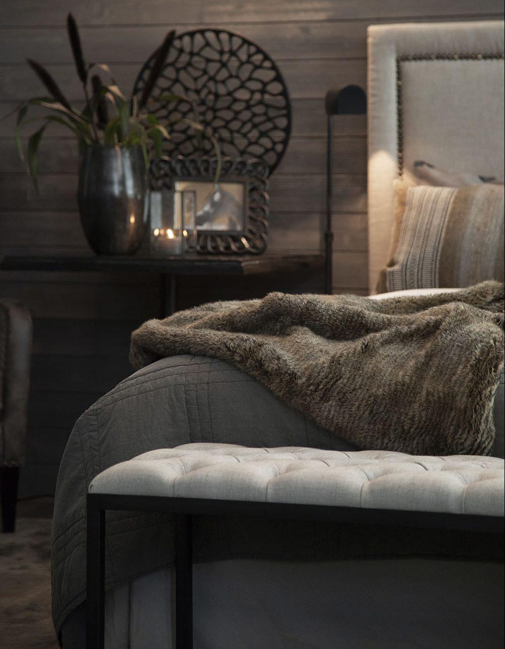 Miljöbild på sänggaveln Paris från Artwood med prydnadskuddar och pläd.