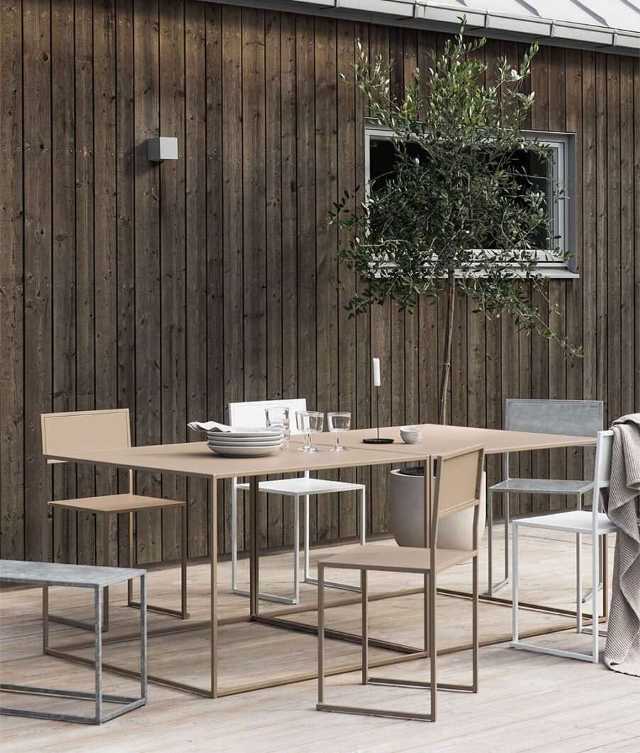Miljöbild på beige matbord från Design Of med stolar i olika färger.