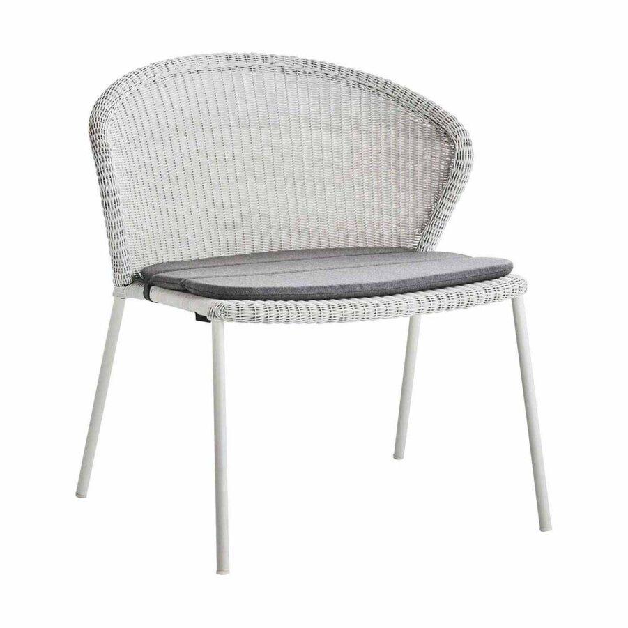 Lean fåtölj i vitgrå konstrotting med grå sittdyna.