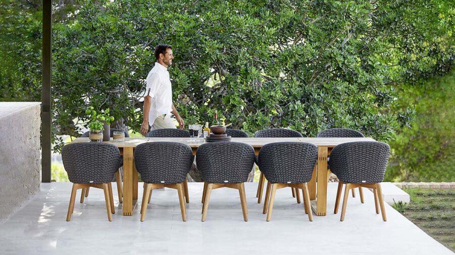 Miljöbild på Peackock karmstol med matbordet Endless i teak från det danska varumärket Cane-Line