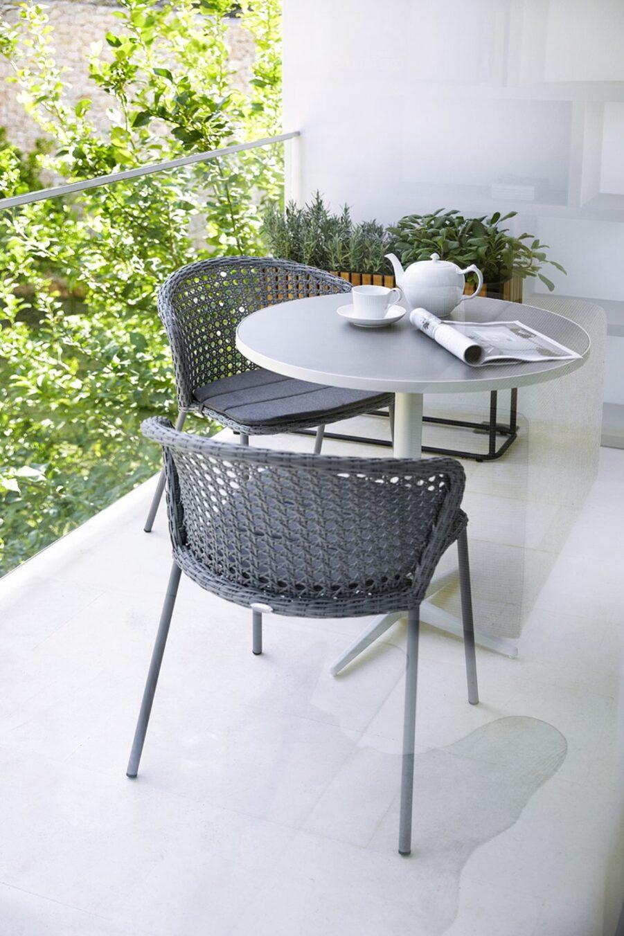 Miljöbild på cafégrupp från Cane-Line i aluminium och konstrotting.
