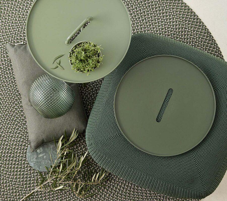 Miljöbild på produkter från Cane-Line i mörkgrönt, bland annat Divine fotpall och On-themove brickbord.
