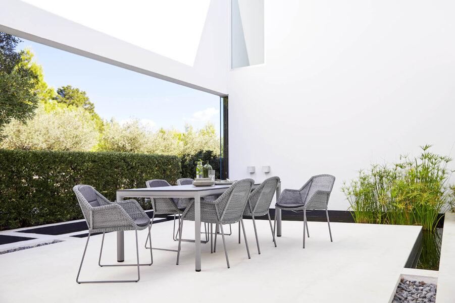 Miljöbild på matgrupp med ljusgråa Breeze-stolar från Cane-Line.