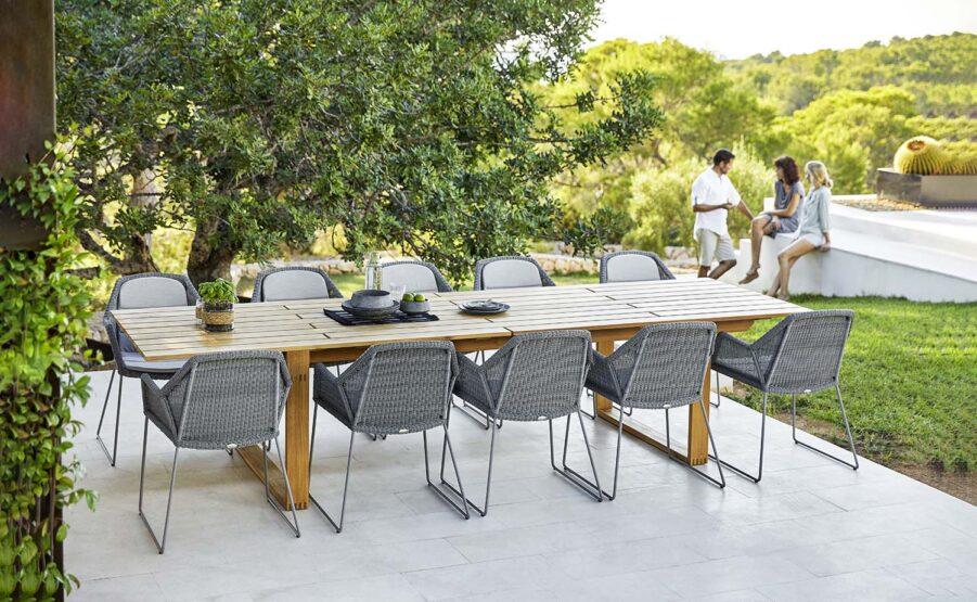 Miljöbild på matbord i teak med ljusgrå karmstolar i serien Breeze.
