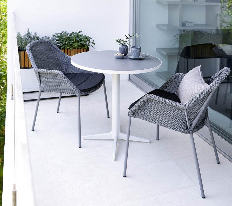 Miljöbild på Breeze stapelstol i ljusgrått med cafébordet Go.