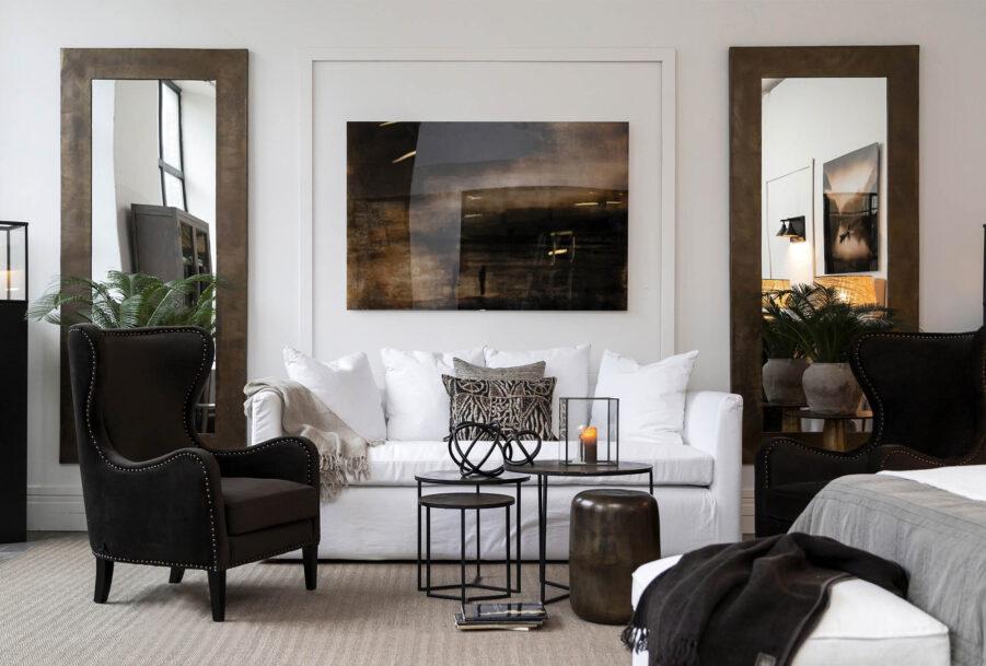 Miljöbild på soffan Coral från Artwood med sidobord och speglar i aluminium.