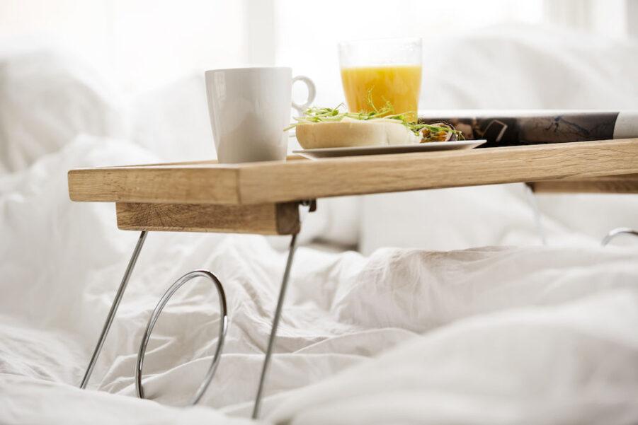 Miljöbild på sängbricka i ek med hopfällbara ben från Sagaform.