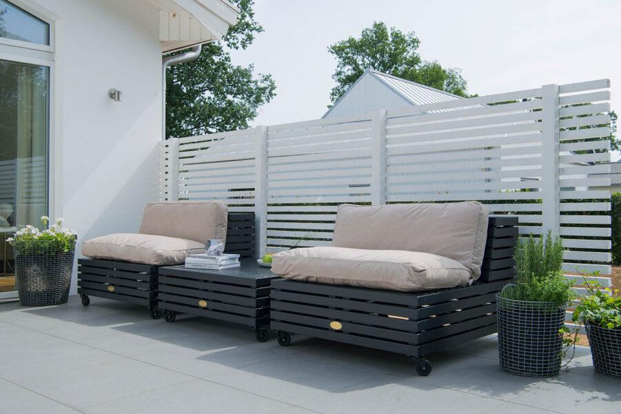 Miljöbild på Bara Vara loungemöbler från Hillerstorp i furu i färgen orkangrå med dynor i linne och polyster.