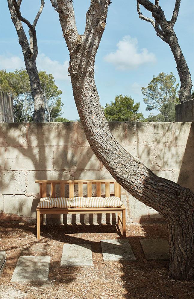 Miljöbild på Plank soffa med vit och gulrandig dyna.