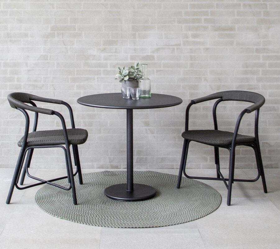 Miljöbild på Noble karmstol med cafébordet Go från Cane-Line.