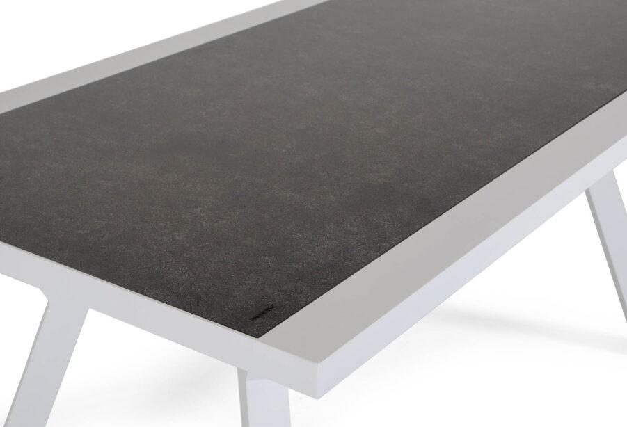 Detaljbild på Como soffbord i vit aluminium och grå glasskiva.