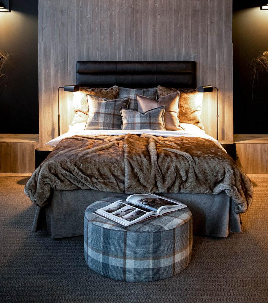 Miljöbild på säng med sänggavel, puff kuddar och överkast från Artwood.