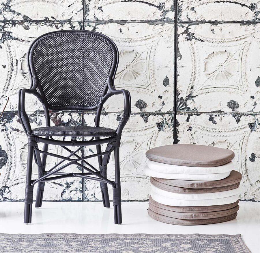 Miljöbild på Rossini karmstol med dynor i vitt och taupe vid sidan.