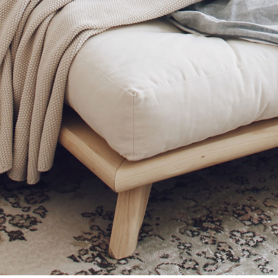Närbild på Senza säng i natur.